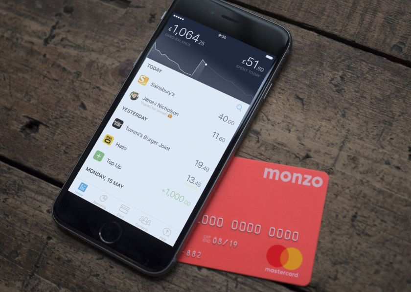 Hot coral Monzo card and iPhone with the Monzo app open.
